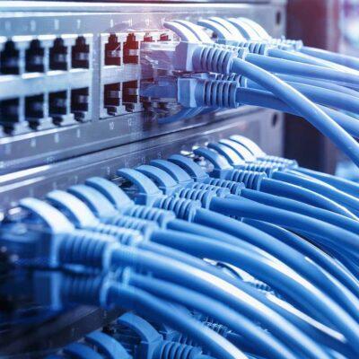 Netzwerkkabel und Hub-Nahaufnahme mit faseroptischem Hintergrund